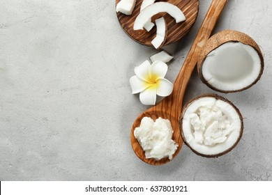 Wooden spoon with fresh coconut oil and nut on table