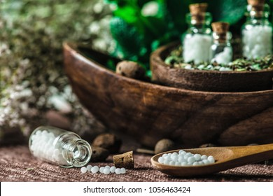 Wooden spoon full of homeopathic globules, small bottles with homeopathic pills andfresh leaves in background