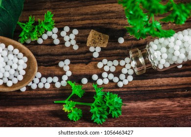 Wooden spoon full of homeopathic globules and small bottles with homeopathic pills, fresh leaves, wooden background, homeopathy concept