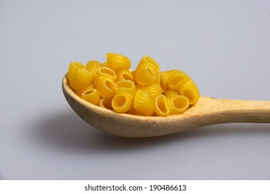 wooden spoon full of macaroni on light grey background