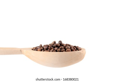 Wooden spoon full with pine nuts.