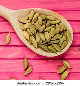 Wooden Spoon Full Of Spicy Indian Cardamom Pods, On A Pink Wooden Background, With No Peopl