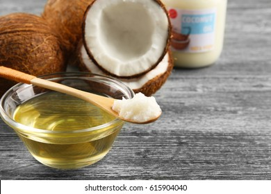 Wooden spoon and glass bowl with oil and coconut on grey background