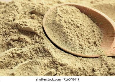 Wooden spoon in hemp protein powder, closeup