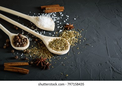 Wooden spoon with Italian seasoning-dried oregano with thyme, basil and vegetables.Oregano in a wooden spoon on a rocky concrete dark black background with a place for text.Top view.salt crystals pep