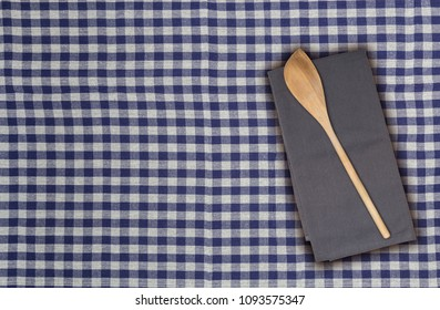 Wooden spoon and kitchen towel on blue white checkered kitchen towel.