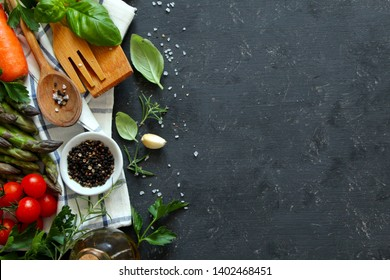 Wooden spoon and knife with ingredients on dark background. Top view with copy space. Cooking concept.