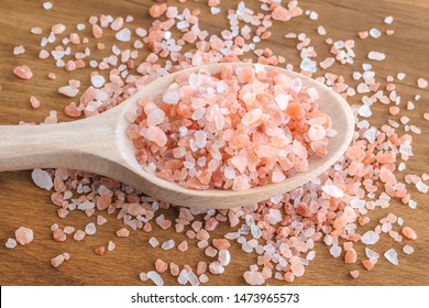 Wooden spoon with large crystals of pink himalayan salt on a brown wooden background. Himalayan salt is used in cooking, medicine and cosmetology. Top view.