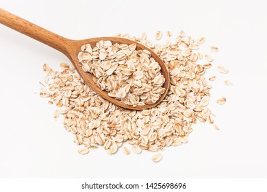 Wooden spoon with oats on white background.