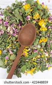 Wooden spoon in a pile of herbs