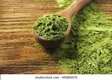 Wooden spoon with powdered matcha green tea on wooden table