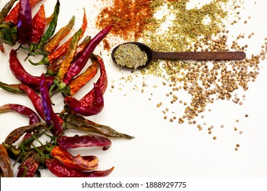 Wooden spoon with rosemary. Dried red peppers. On a white background.