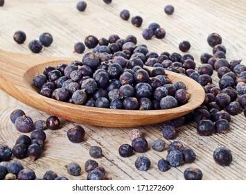 Wooden spoon with seeds of juniper. Selective focus