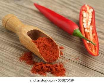 a wooden spoon with spice red paprika