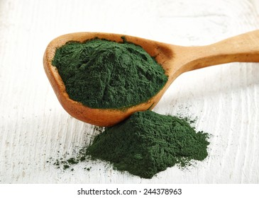 Wooden spoon of spirulina algae powder on white wooden background