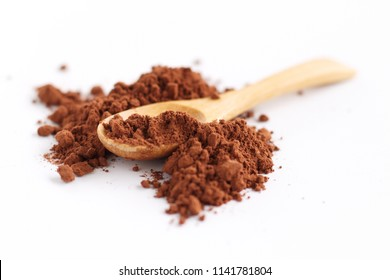 A wooden spoon surrounded by cocoa powder over a white background. the powder contains flavonoids with the function as antioxidants that help prevent systemic inflammation.