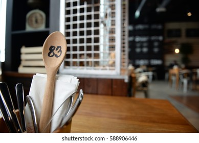 Wooden Spoon Table Number in a Stylish Cafe, with Serviettes and a Wooden Table