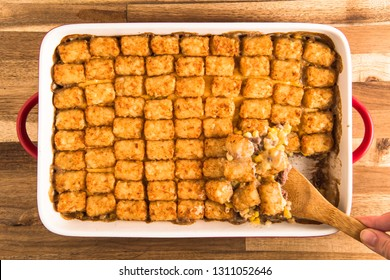 A wooden spoon taking a scoop from a pan of tater tot hot dish, shot from above on a wooden countertop.