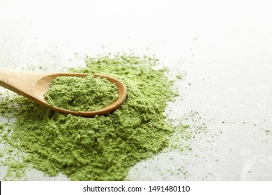 Wooden spoon with wheat grass powder on light table, closeup. Space for text