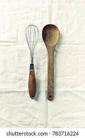 Wooden Spoon and Whisk on white linen cloth; flatlay