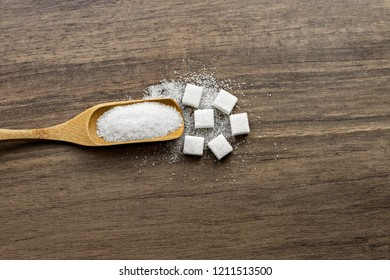 Wooden spoon and white sugar on wooden table. Background.