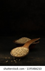 A wooden spoonful of sesame seeds in a low light with copy space background