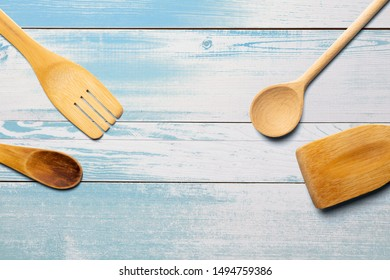 Wooden spoons, fork and stirrer on turquoise wooden table. Kitchen and Cooking Concept.