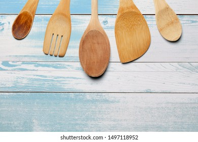 Wooden spoons, fork and stirrer on turqoise wooden table. Kitchen and cooking concept.