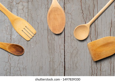 Wooden spoons, fork and stirrer on gray wooden table. Kitchen and Cooking Concept.