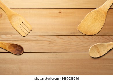 Wooden spoons, fork and stirrer on wooden table. Kitchen and Cooking Concept.