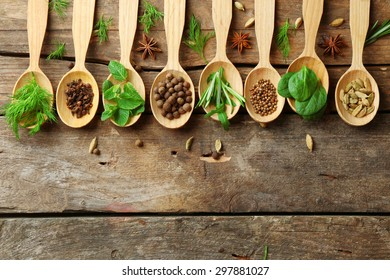 Wooden spoons with fresh herbs and spices on wooden background