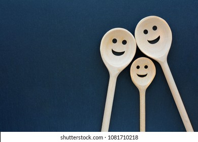 Wooden spoons look like happy family. Smiling faces.