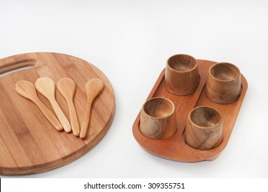 Wooden spoons on the kitchen board with wooden bowls.