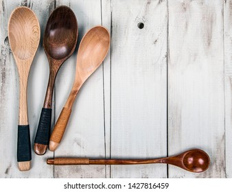 Wooden spoons on rustic, vintage, natural wood - cooking and kitchen menu background, with design space.
