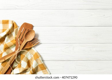Wooden spoons and other cooking tools with brown napkins on the kitchen table.