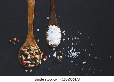 wooden spoons with pepper and salt on a blackboard base, top view with copy space. Cooking ingredients and condiments concept.