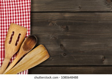 Wooden spoons with red and white kitchen towel on white wooden table with copy space