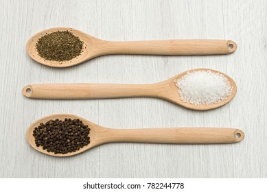 wooden spoons with salt, pepper and oregano on table.