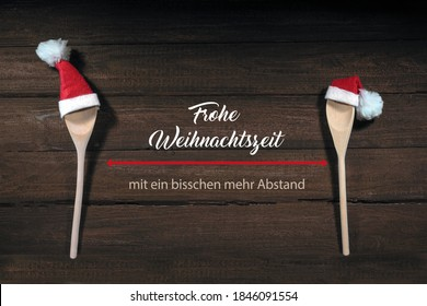 Wooden spoons with Santa Claus hats, German text Frohe Weihnachtszeit mit ein bisschen Abstand, meaning Merry Christmas with social distance, rustic wooden background, health concept against covid-19