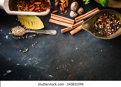 wooden spoons with spices and herbs on textured black table