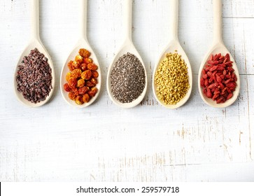 Wooden spoons of various superfoods on white wooden background