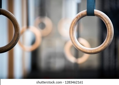Wooden sport rings in gym, viewed in close-up with selective focus. Pair of rings is blurred in background. Gymnastics equipment concept