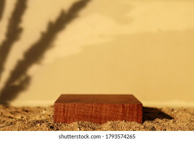 Wooden square pedestal on sand. Beige background, plant shadow. Monochrome brown template for banner, poster. Mockup for natural product, eco cosmetic packaging. Sultry mood. Hard sunlight trend
