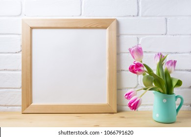 Wooden square picture frame mockup with pink tulip in mint pitcher vase near painted brick wall. Empty frame mock up for presentation design. Template framing for modern art.