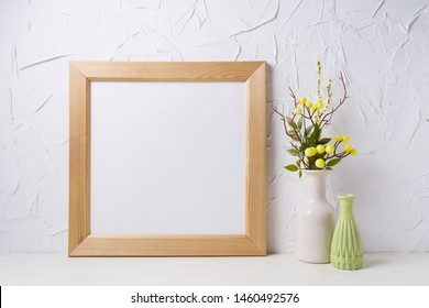 Wooden square picture frame mockup with yellow decorated branches and green vase. Empty frame mock up for presentation design. Template framing for modern art.