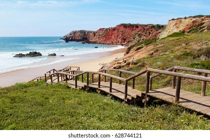 A wooden staircase in azure sea with rocks