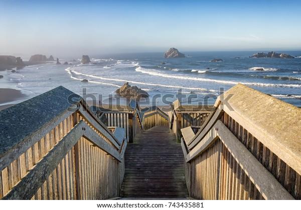 Wooden staircase leading to the coast Bandon Beach at sunrise, Oregon, USA