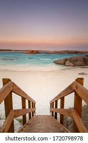 Wooden staircase leading down to a beach at dusk with orange granite rocks in the water and soft color in the sky caused by bush fire smoke haze at Twilight Cove, Esperance, Western Australia