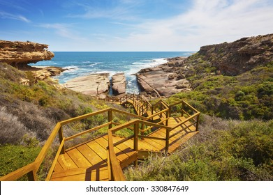 Wooden staircase leading down to a rugged, untouched coastline.