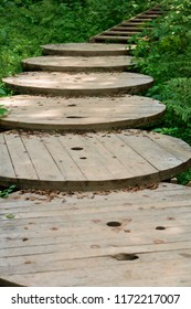 wooden staircase with railing on the slope, stairs for descent to the sea